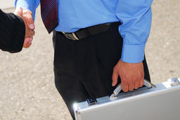 Businessman with briefcase extending a handshake to a colleague Photo