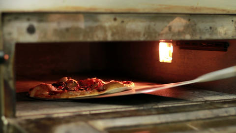 Cook Pulls A Pizza Out Of The Oven Stock Video Footage
