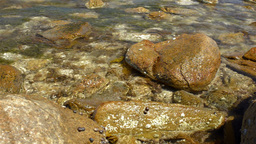 Small Wave Washing onto Rocks in a Bay Stock Video Footage