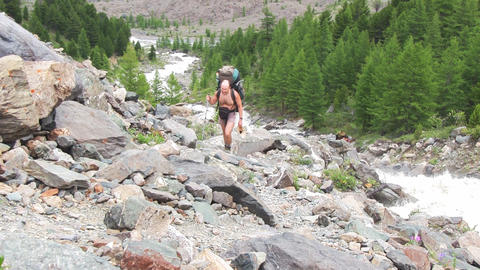 Man with backpack hiking across mountain Stock Video Footage