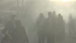Kashgar street people walking through smoke Footage