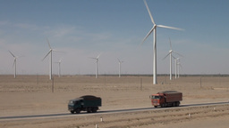 Trucks drive in front of Chinese wind farm Stock Video Footage