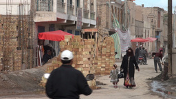 Woman in burqah walks through construction in Kash Stock Video Footage