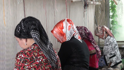 Veiled women making carpets in Xinjiang editorial Footage
