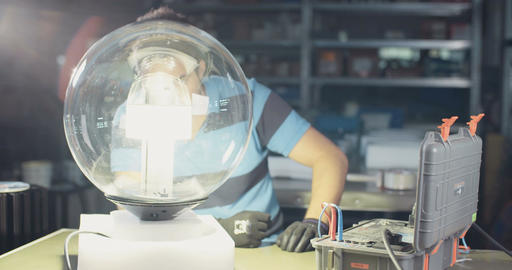 Technician testing LED lamp in an electronics and lighting manufacturing facilit Live Action