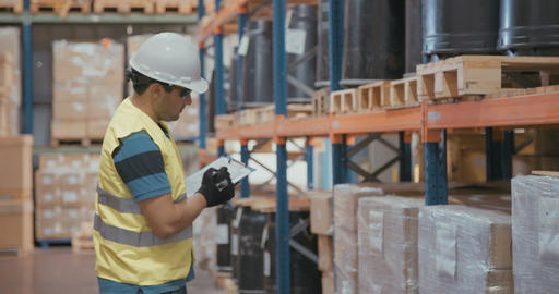 Man wearing a helmet working in a large industrial warehouse Live Action