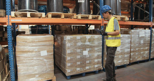 Young man wearing a helmet inspecting inventory in an industrial warehouse Live Action