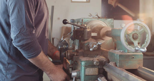Man working on a wooden lathe creating art objects Live Action