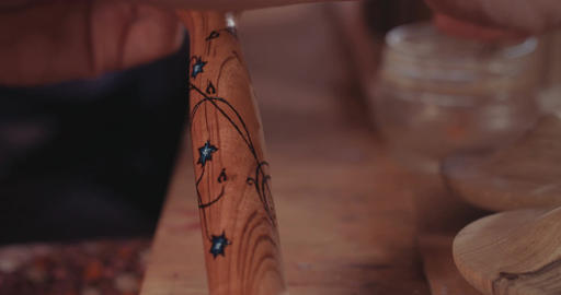 Artist painting wooden Buddhist prayer wheels with lacquer Footage
