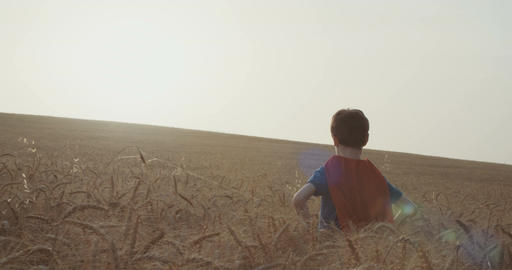 Superhero boy standing in a golden wheat field during sunset Live Action