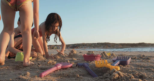 Three kids playing at the beach, enjoying the waves and building sand castles Footage