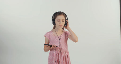 Girl listening to music from a mobile phone with earphones and dancing Filmmaterial