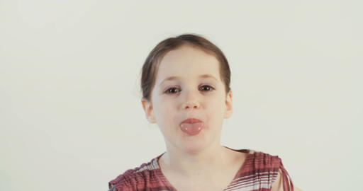 Little girl pulling out tongue to the camera on white background Footage
