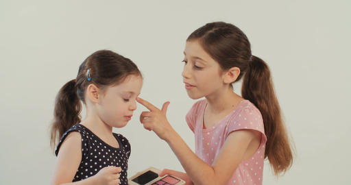 Girl helping her little sister put on make-up on white background Footage