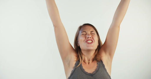 Young blonde woman acting surprised and happy on a white studio background Footage