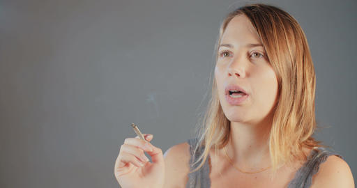 Young blonde woman smoking on a gray background Footage