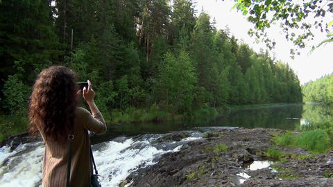 Woman taking pictures of forest river Footage