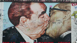 Famous male kiss of Brezhnev and Honecker at the Berlin Wall. Zoom out shot Footage