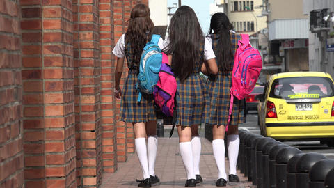 Teen Female Students Walking On Sidewalk