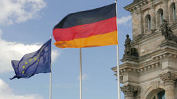 EU and German flag on the front of The Reichstag building in Berlin Footage