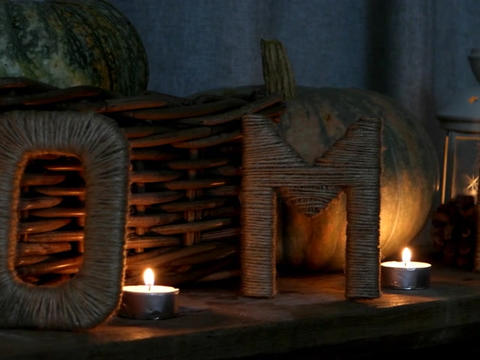 Letters drawn up in the form of the word HOME with pumpkins, pine cones by candl Live Action