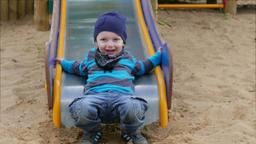 Boy sliding down on slide. Happy boy on a playground Footage