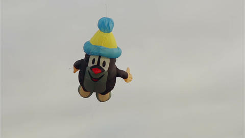 Figurative mole kite flying in front of cloudy sky Footage