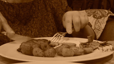 Woman is having dinner, old style sepia view with grain Footage