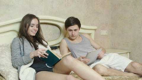 Two young people reading a book, working with a digital tablet GIF