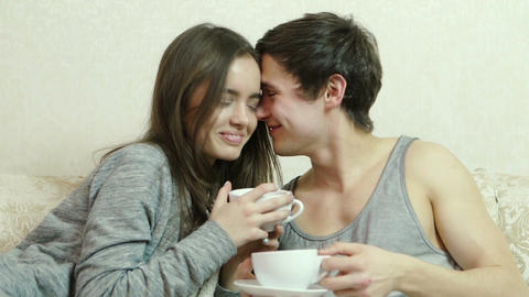Loving couple with cups in their hands flirting with each other GIF