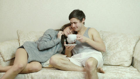 Young girl leaned against a guy flirts gently to him. Man drinking tea (coffee) Footage