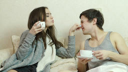 Young girl flirts, grabs the nose of Man, drink tea (coffee) Footage