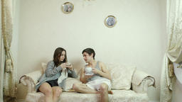 Man and woman drinking tea (coffee) in the living room Footage