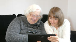 Old woman is watching pictures on tablet computer Footage
