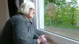 Senior woman is looking throu window Footage