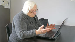 Old woman in a funny mood is listening music on her laptop computer Live Action