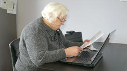 Senior woman is checking her paperwork. Bills, taxes Footage