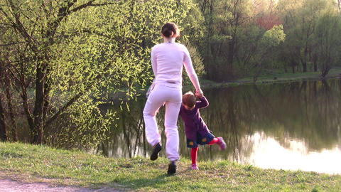 mother with girl on spring pond Stock Video Footage