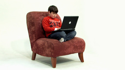 Boy on couch cross legged HD Stock Video Footage