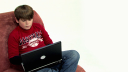 Boy on couch using laptop HD Stock Video Footage