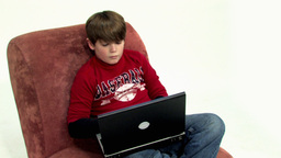 Boy on couch using laptop HD Footage