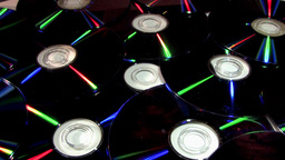 Medium Shot Of Compact Discs (CDs) Rotating With Reflective Surfaces Footage