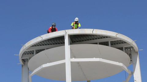 Two Construction Workers Working On Tower Stock Video Footage