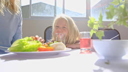 Little Blonde Girl Sits at Table Drinks Juice Near Mother Eating Breakfast Footage