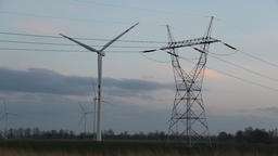 Wind farm and power lines at dusk. Renewable energy sources Footage