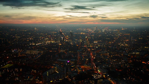 Aerial panning shot of the West London skyline during late evening with street l Footage
