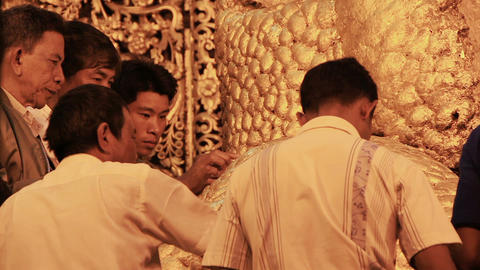 believers worship the Buddha statue and paste gold leaf petals at Mahamuni Buddh Footage