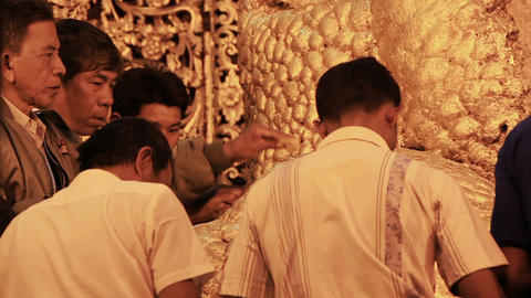 believers worship the Buddha statue and paste gold leaf... Stock Video Footage