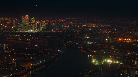 Night aerial shot of the illuminated Thames banks and Canary Wharf in London, En Footage