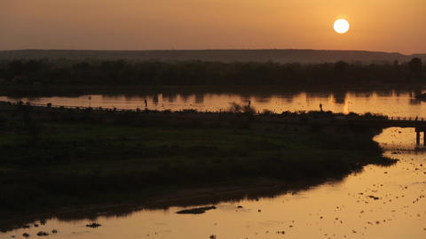 African golden sunset by the Niger river with bridge and boats Footage